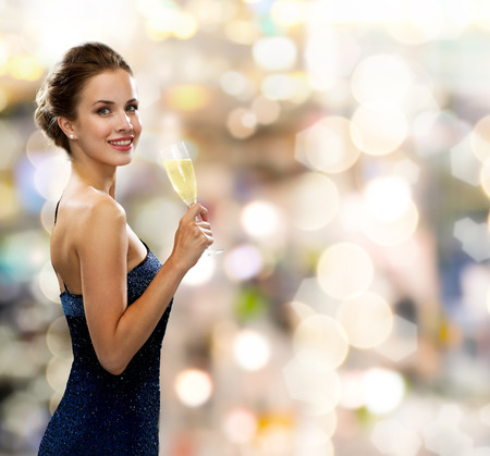 party, drinks, holidays, luxury and celebration concept - smiling woman in evening dress with glass of sparkling wine over lights background Stockfoto