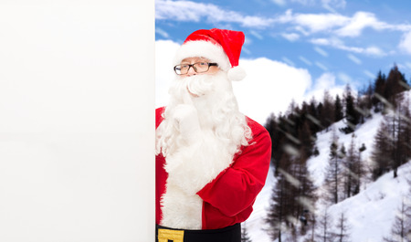 christmas, holidays, advertisement and people concept - man in costume of santa claus with white blank billboard making hust gesture over snowy mountains photo