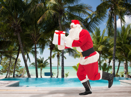 costume party: christmas, holidays, travel and people concept - man in costume of santa claus running with gift box over swimming pool on tropical beach background Stock Photo