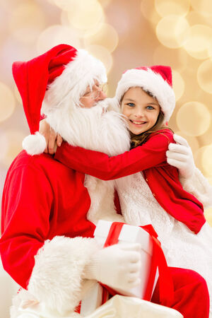 surprise party: holidays, christmas, childhood and people concept - smiling little girl hugging with santa claus over beige lights background