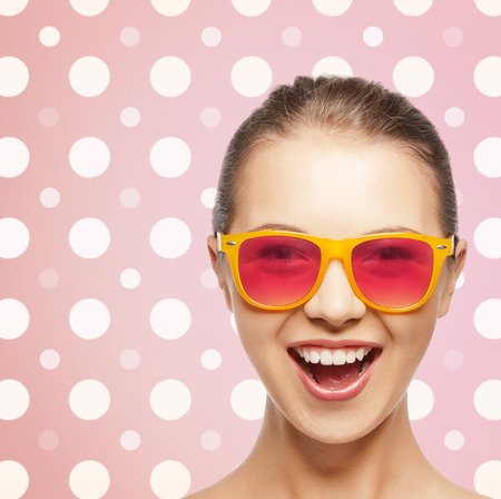 happiness, holidays, fashion and people concept - happy laughing teenage girl in shades over pink and white polka dots pattern background photo