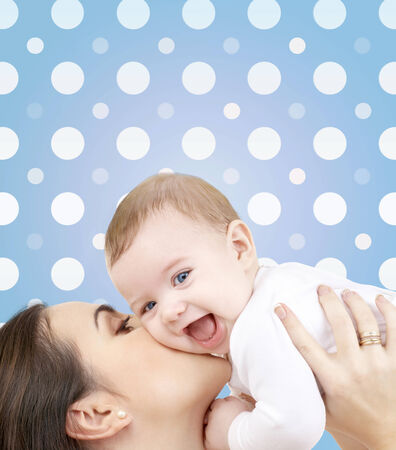 baby with mama: motherhood, children, adoption, happiness and people concept - happy mother kissing her baby boy over blue and white polka dots pattern background Stock Photo