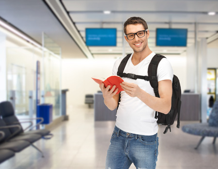 travel, education, tourism and people - smiling student with backpack and book at airport Фото со стока