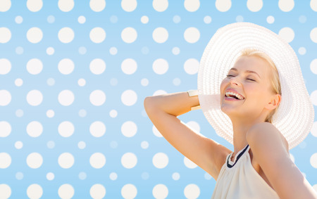 fashion, happiness and people concept - beautiful smiling woman in white summer hat over blue and white polka dots pattern background