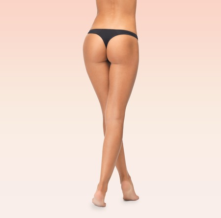 bikini butt: beauty, people and bodycare concept - close up of female legs in black bikini panties over pink background Stock Photo