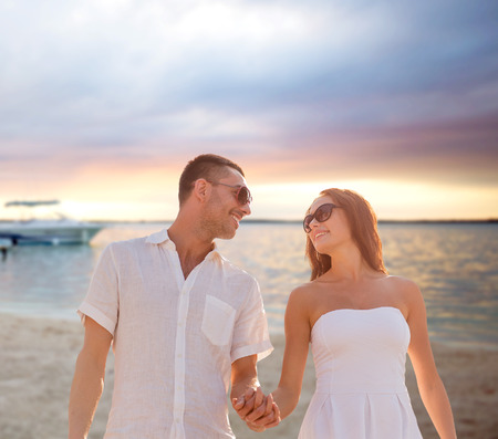 love, people, travel, summer and relations concept - smiling couple wearing sunglasses walking outdoors over beach background photo