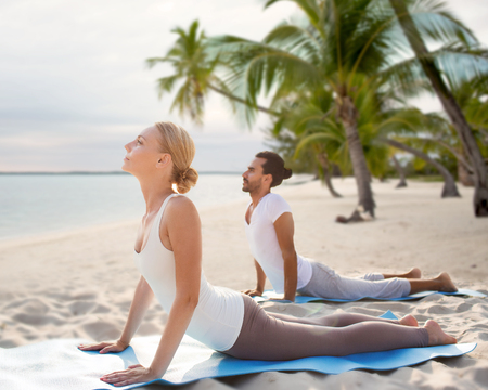 beach mat: fitness, sport, yoga, people and lifestyle concept - happy couple making yoga exercises on tropical beach