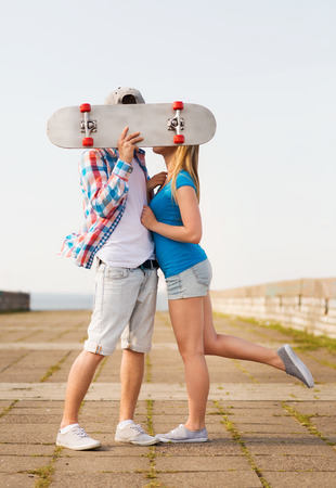 cute teen girl: holidays, vacation, love and people concept - couple kissing and hiding their faces behind skateboard outdoors