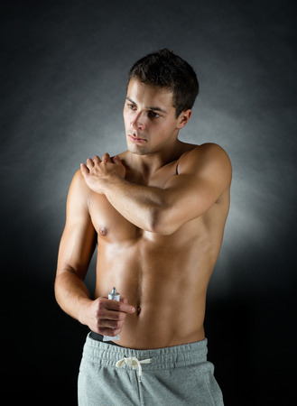 pain relief: sport, bodybuilding, medicine and people concept - young man standing over black background and applying pain relief gel on his shoulder
