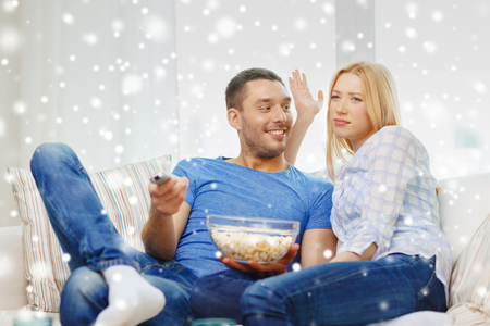 family sofa: love, family, technology, entertainment and people concept - smiling couple watching tv and lying on sofa at home