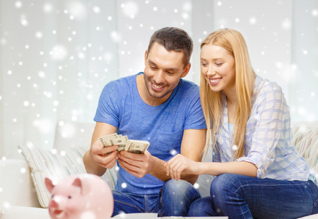 love, family, finance, money and happiness concept - smiling couple counting money with piggybank on table at home Stock Photo