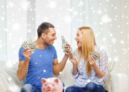 love, family, finance, money and happiness concept - happy couple with cash money and piggybank cheering at home Stock Photo