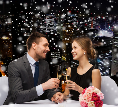 clinking: celebration, christmas, holidays and people concept - smiling couple clinking glasses of sparkling wine at restaurant over snowy night city background Stock Photo