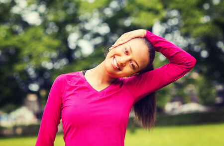 stretches: fitness, sport, training, park and lifestyle concept - smiling woman stretching leg outdoors