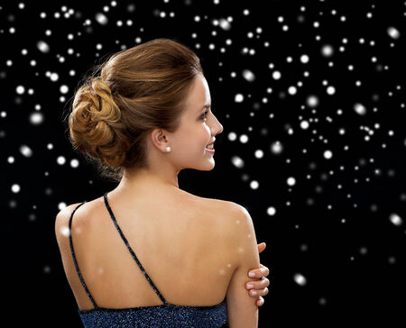 traje de gala: gente, fiestas y glamour concepto - mujer sonriente en traje de noche sobre fondo negro cubierto de nieve de la parte posterior