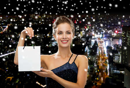 holydays: luxury, advertisement, holydays and sale concept - smiling woman with white blank shopping bag over snowy night city background