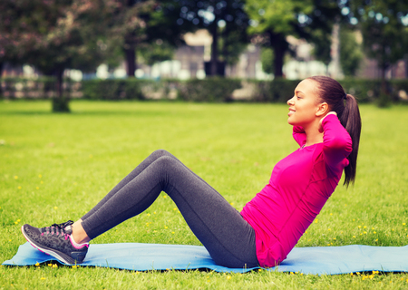 pretty black woman: fitness, sport, training, park and lifestyle concept - smiling woman doing exercises on mat outdoors