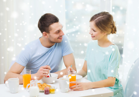 food, home, people and happiness concept - smiling couple having breakfast at home photo