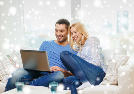 love, family, technology, internet and happiness concept - smiling happy couple with laptop computer at home photo