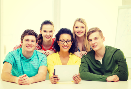 education, technology and college concept - five smiling students with tablet pc computer at school photo