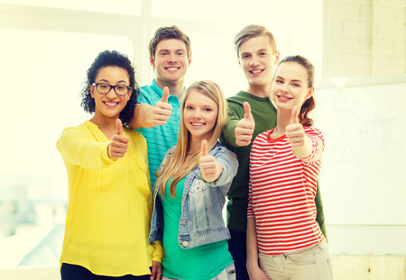 education and school concept - five smiling showing thumbs up at school