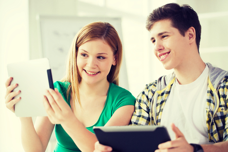 teenage guy: education, technology and internet concept - smiling students with tablet pc computers at school