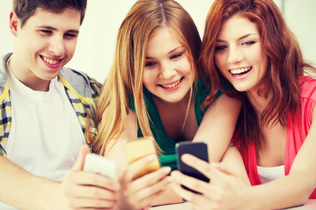 taking video: education, relationships and technology concept - three smiling students with smartphone at school Stock Photo