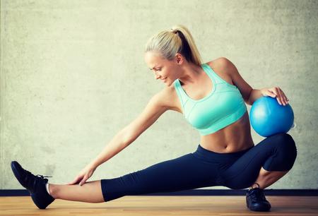 ejercicio aer�bico: fitness, deporte, entrenamiento y estilo de vida concepto - mujer sonriente con bola de ejercicio en el gimnasio Foto de archivo