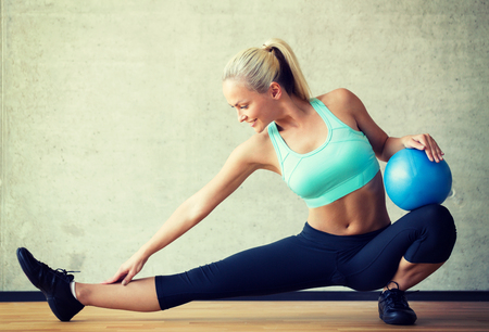 exercises: fitness, sport, training and lifestyle concept - smiling woman with exercise ball in gym Stock Photo