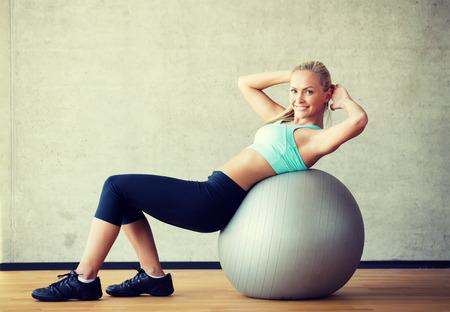 aerobics: fitness, deporte, entrenamiento y estilo de vida concepto - mujer sonriente con bola de ejercicio en el gimnasio Foto de archivo