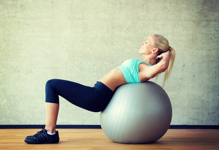 fitness, sport, training and lifestyle concept - smiling woman with exercise ball in gym Reklamní fotografie
