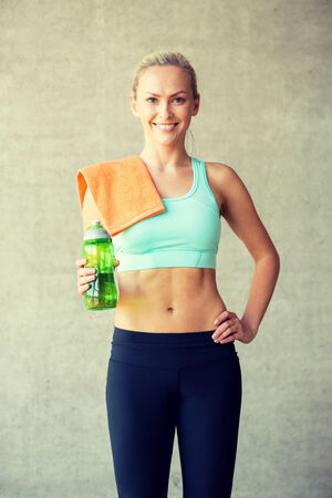 perfect fit: fitness, sport, training, drink and lifestyle concept - woman with bottle of water in gym Stock Photo