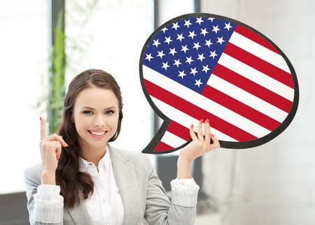foreign country: education, foreign language, english, people and communication concept - smiling woman holding text bubble of american flag Stock Photo