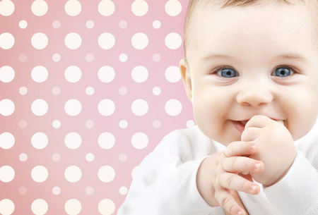 childhood, people and happiness concept - smiling baby girl face over pink and white polka dots pattern