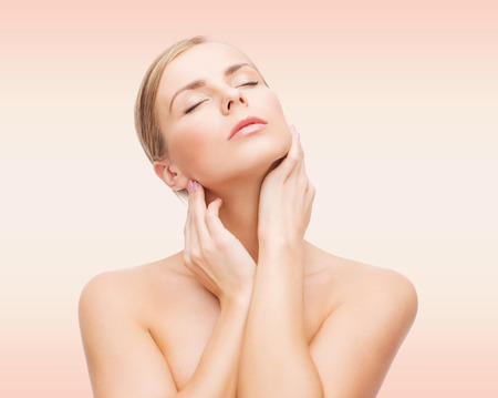 woman neck: beauty, people and health concept - beautiful young woman with closed eyes touching her neck over pink background