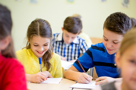 elementary kids: education, elementary school, learning and people concept - group of school kids with pens and notebooks writing test in classroom
