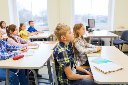 education, elementary school, learning and people concept - group of school kids with notebooks sitting in classroom Stock Photo