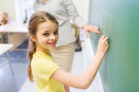 colegiala: educación, escuela primaria, el aprendizaje, las matemáticas y la gente concepto - pequeño sonriente escribir números colegiala en tarjeta de tiza verde en el aula Foto de archivo