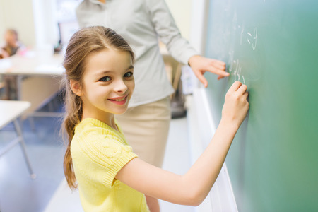 math: education, elementary school, learning, math and people concept - little smiling schoolgirl writing numbers on green chalk board in classroom
