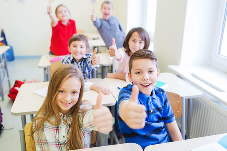 learners: education, elementary school, learning, gesture and people concept - group of school kids sitting in classroom and showing thumbs up
