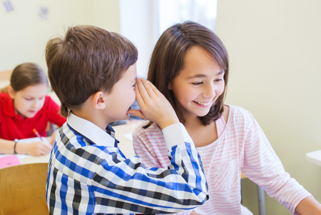 education, elementary school, learning and people concept - smiling schoolboy whispering secret to classmate ear in classroom Stock Photo