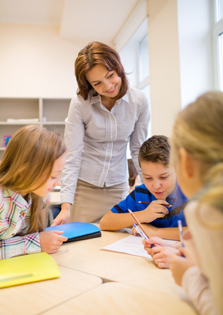 elementary student: education, elementary school, learning and people concept - teacher helping school kids writing test in classroom