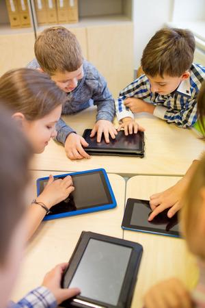 salle de classe: l'�ducation, l'�cole primaire, l'apprentissage, la technologie et les gens notion - groupe d'enfants de l'�cole avec l'ordinateur tablette pc en se amusant sur la rupture dans la classe
