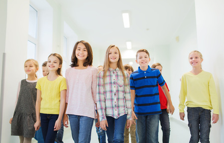 asian school girl: education, elementary school, drinks, children and people concept - group of smiling school kids walking in corridor
