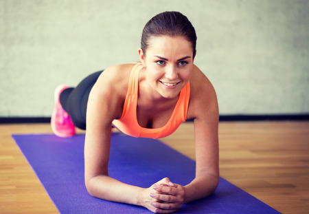 planks: fitness, sport, training and lifestyle concept - smiling woman doing exercises on mat in gym