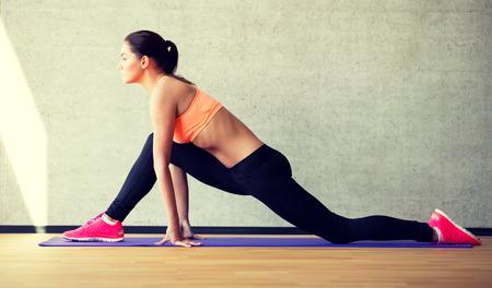gym: fitness, deporte, entrenamiento y estilo de vida concepto - mujer sonriente que se extiende la pierna sobre colchoneta en el gimnasio