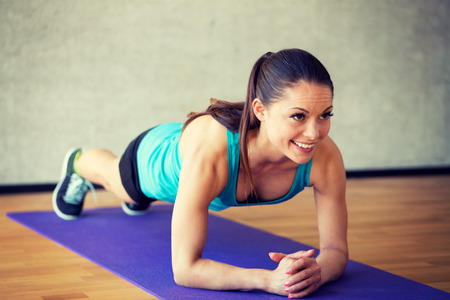 home gym: fitness, sport, training and lifestyle concept - smiling woman doing exercises on mat in gym