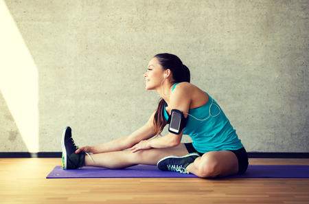home gym: fitness, sport, training and lifestyle concept - smiling woman stretching leg on mat in gym Stock Photo