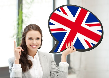 foreign national: education, foreign language, english, people and communication concept - smiling woman holding text bubble of british flag and pointing finger up