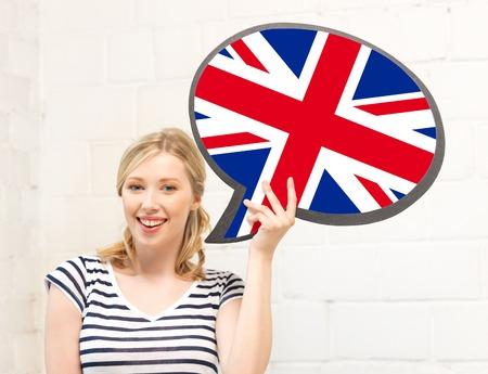 bandera inglesa: educación, idioma fogeign, inglés, personas y comunicación concepto - mujer sonriente que sostiene la burbuja de texto de bandera británica